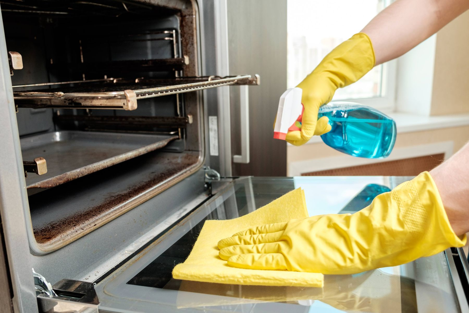 hand cleaning oven glass door