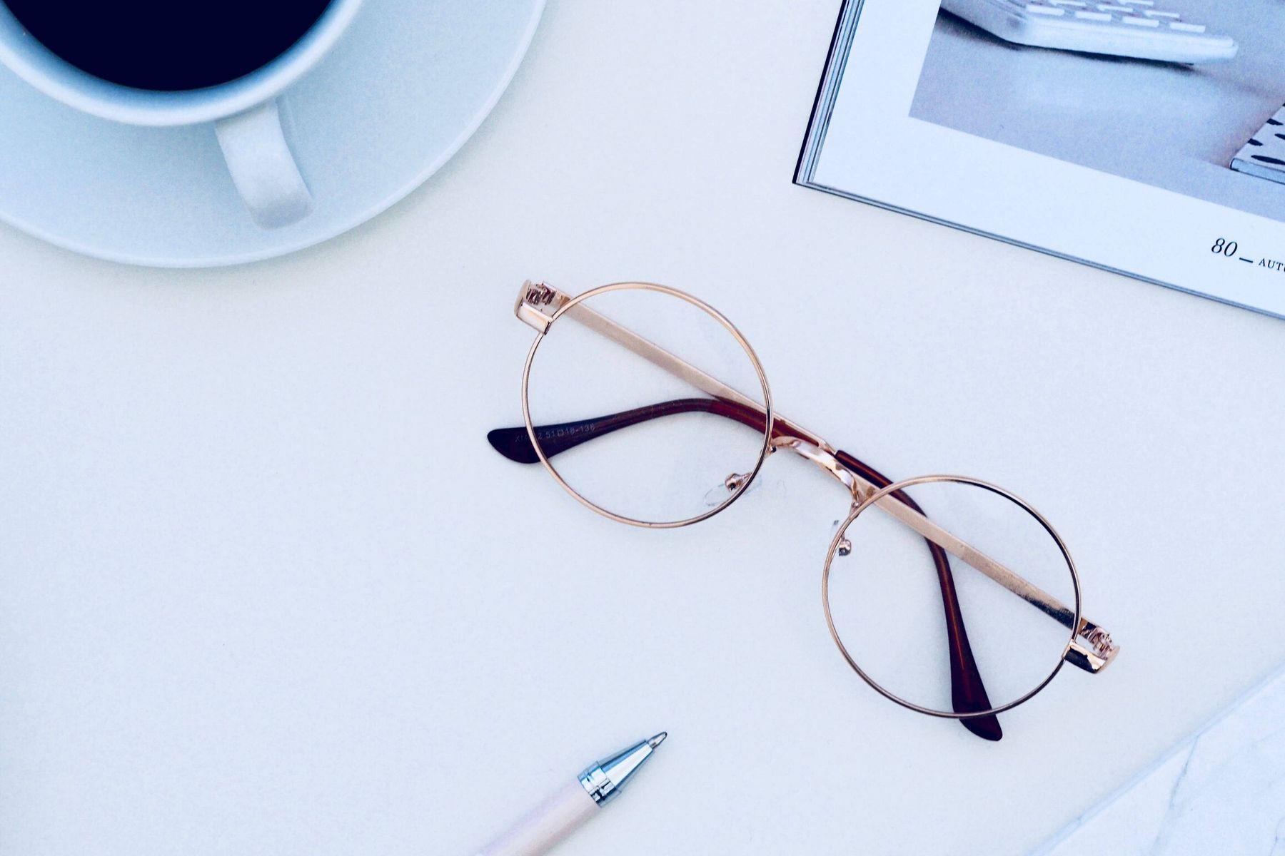 Brille auf Tisch mit Kaffetasse