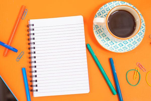 Telli not defteri, kalemler ve fincanda kahve
