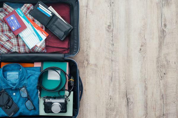 Mala de viagem escura e aberta com camisa azul, camisa xadrez, carteira, óculos, cinto, máquina fotográfica e outros acessórios masculinos, num fundo de madeira
