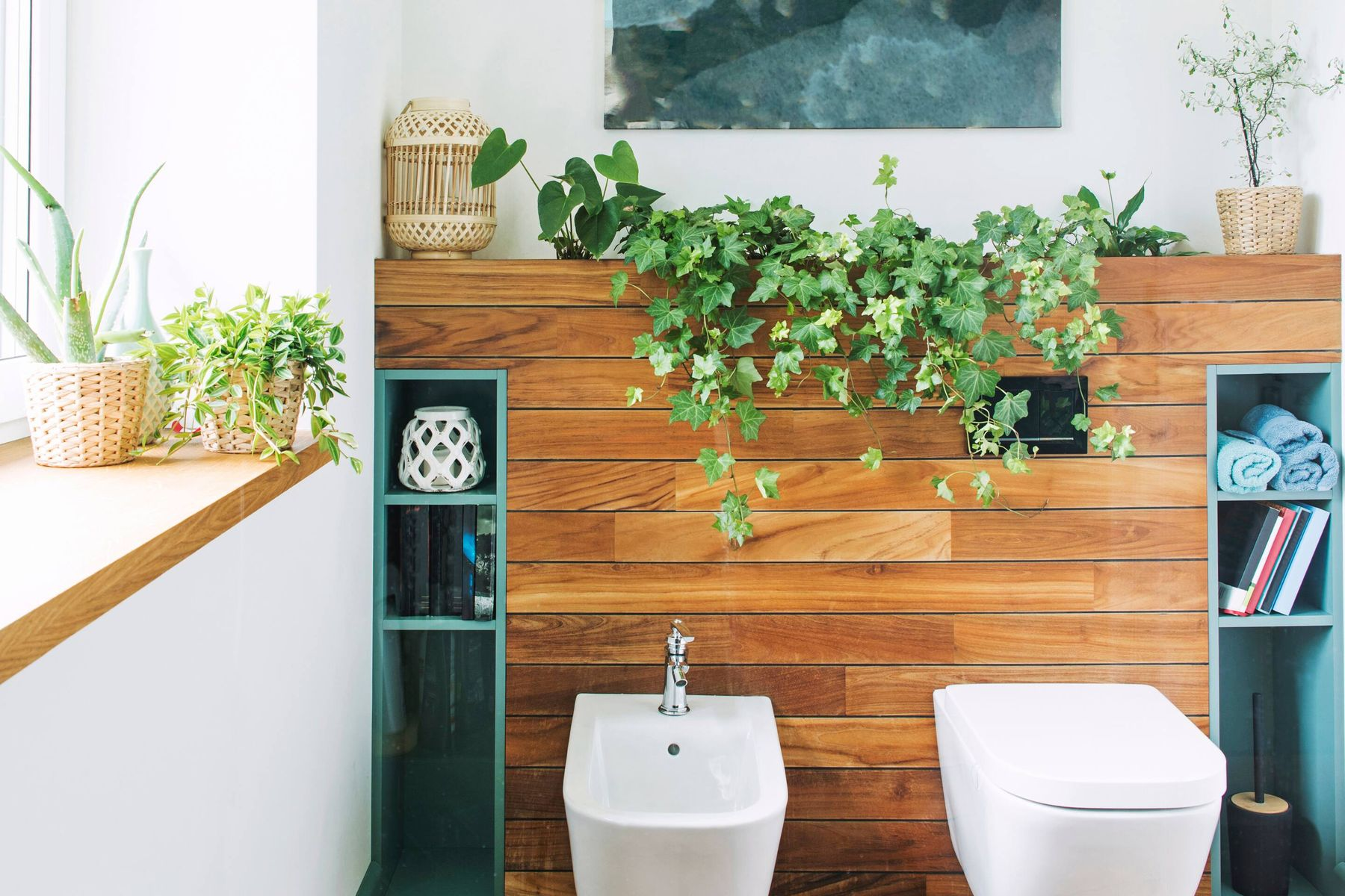Interior of a bathroom with wooden sconces and plants.