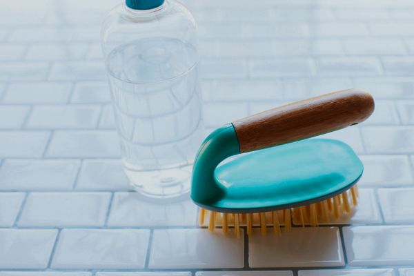 Scrubbing brush on a tiled floor with a grout cleaner solution on the side