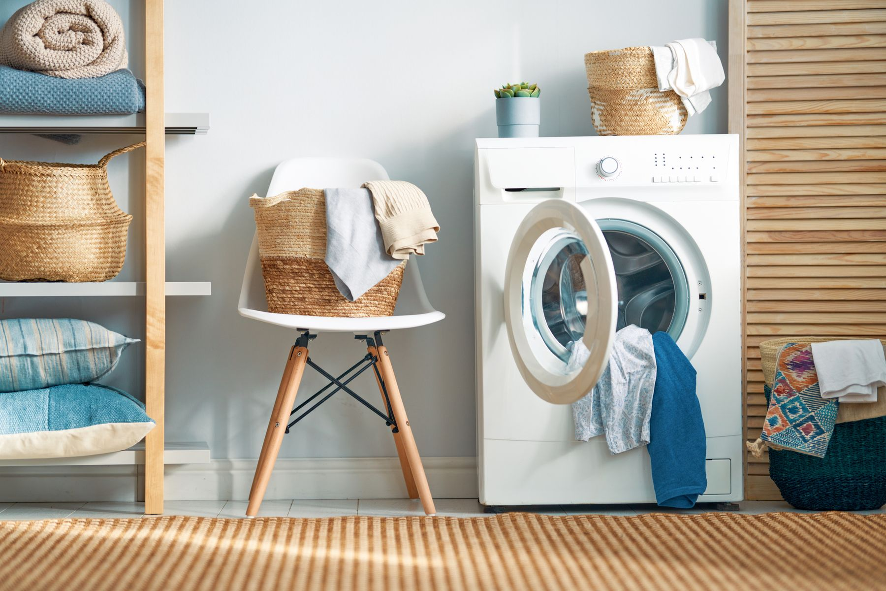 Open tumble dryer with clothes, beside a basket of clothes on a chair in a laundry room