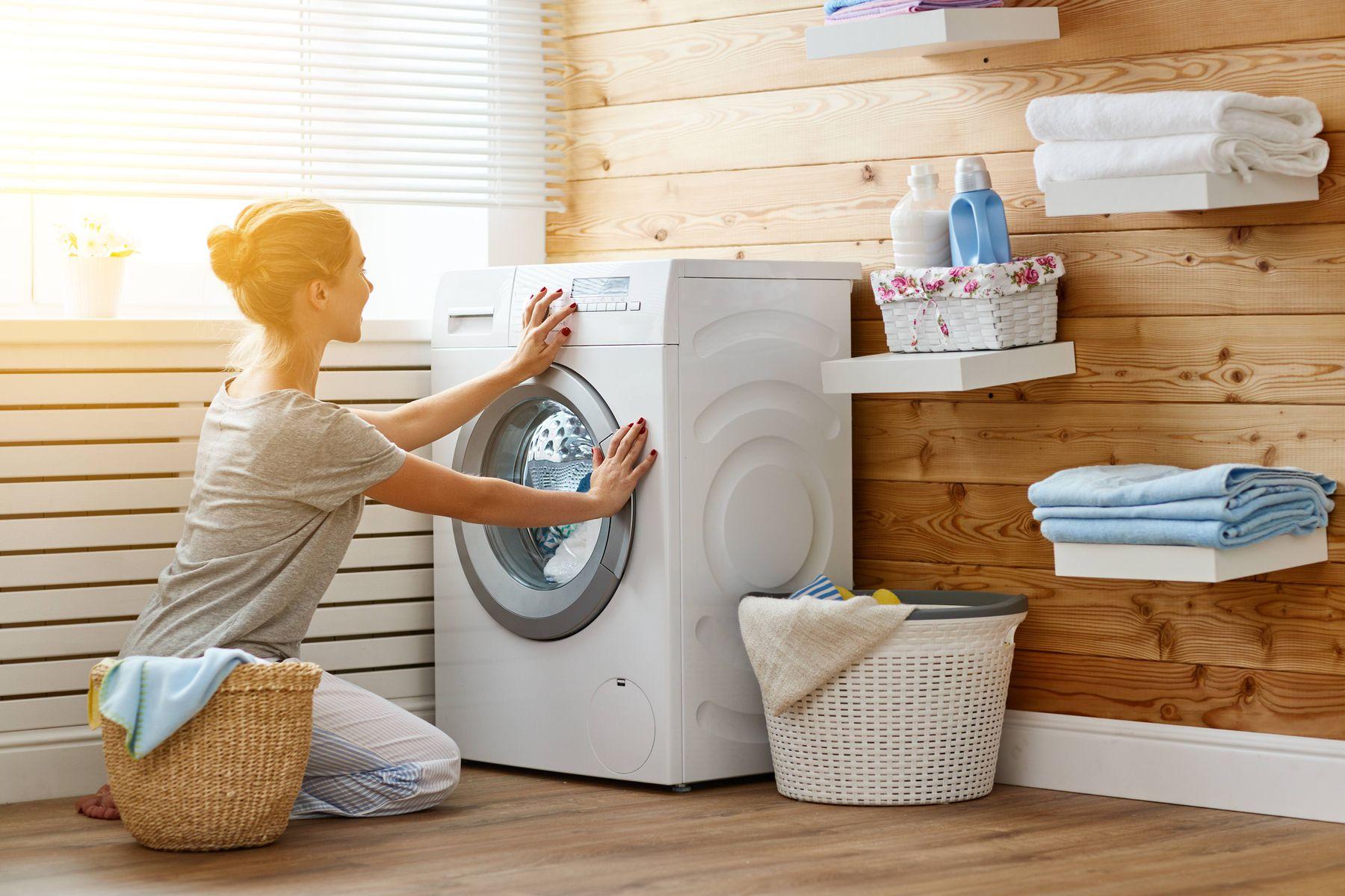 Mulher em lavanderia, fechando a máquina de lavar, com cesto de roupas ao lado e produtos de lavagem e toalhas em prateleiras