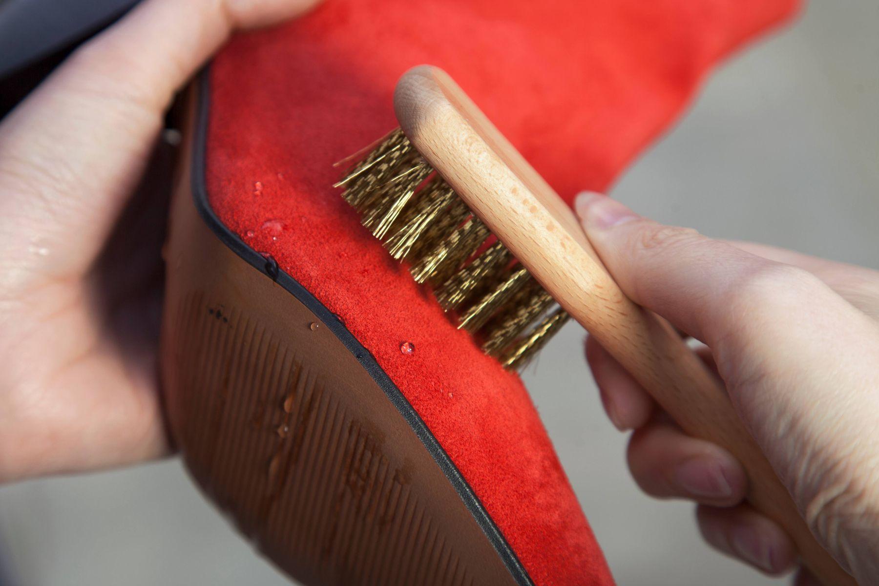 Sapato vermelho de carmuça sendo limpo com escovinha