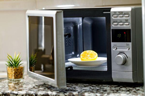 Microondas aberto com um prato branco e um limão cortado sobre o prato