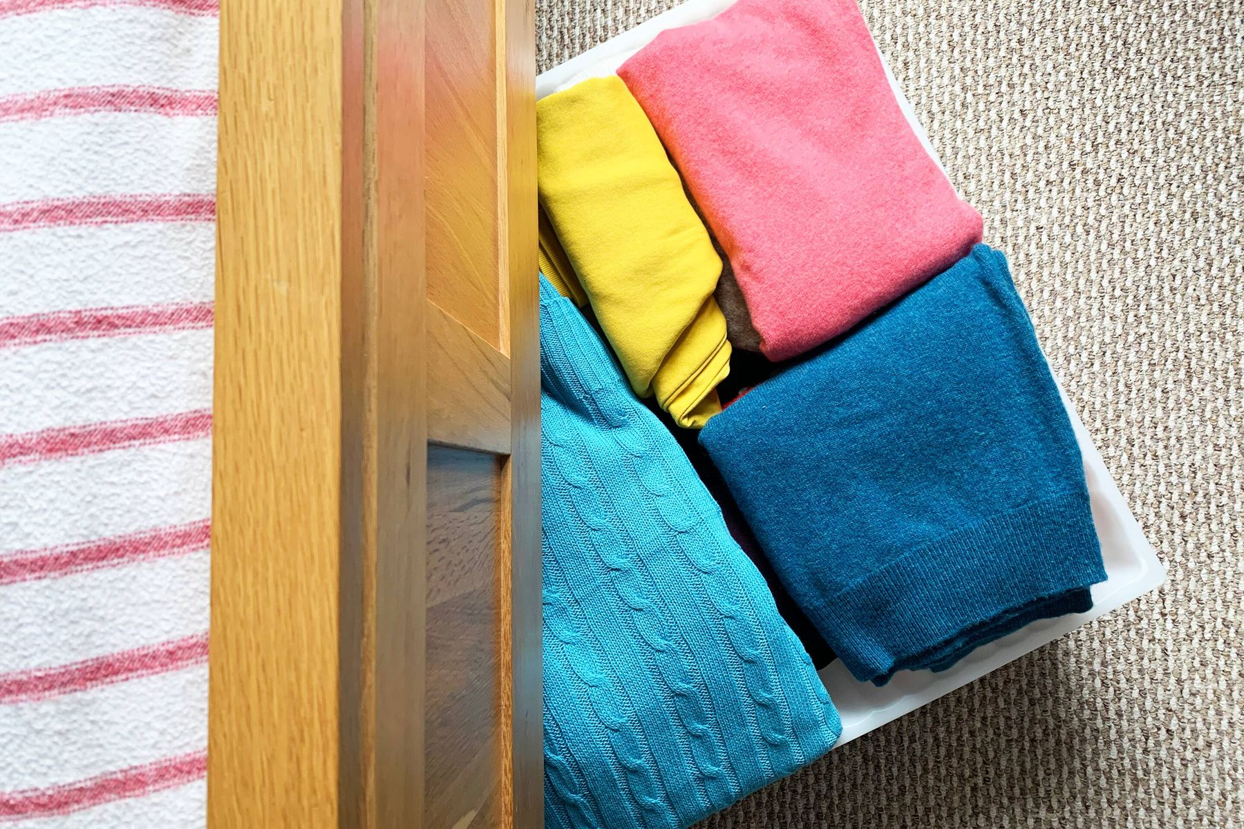 box with colorful clothes stored under the bed