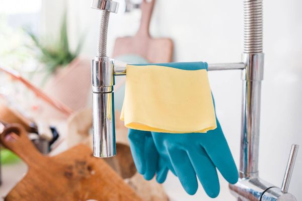 ถุงมือยางสีน้ำเงินและผ้าทำความสะอาดเหลืองเหนือก๊อกน้ำอ่างล้างจานในครัว