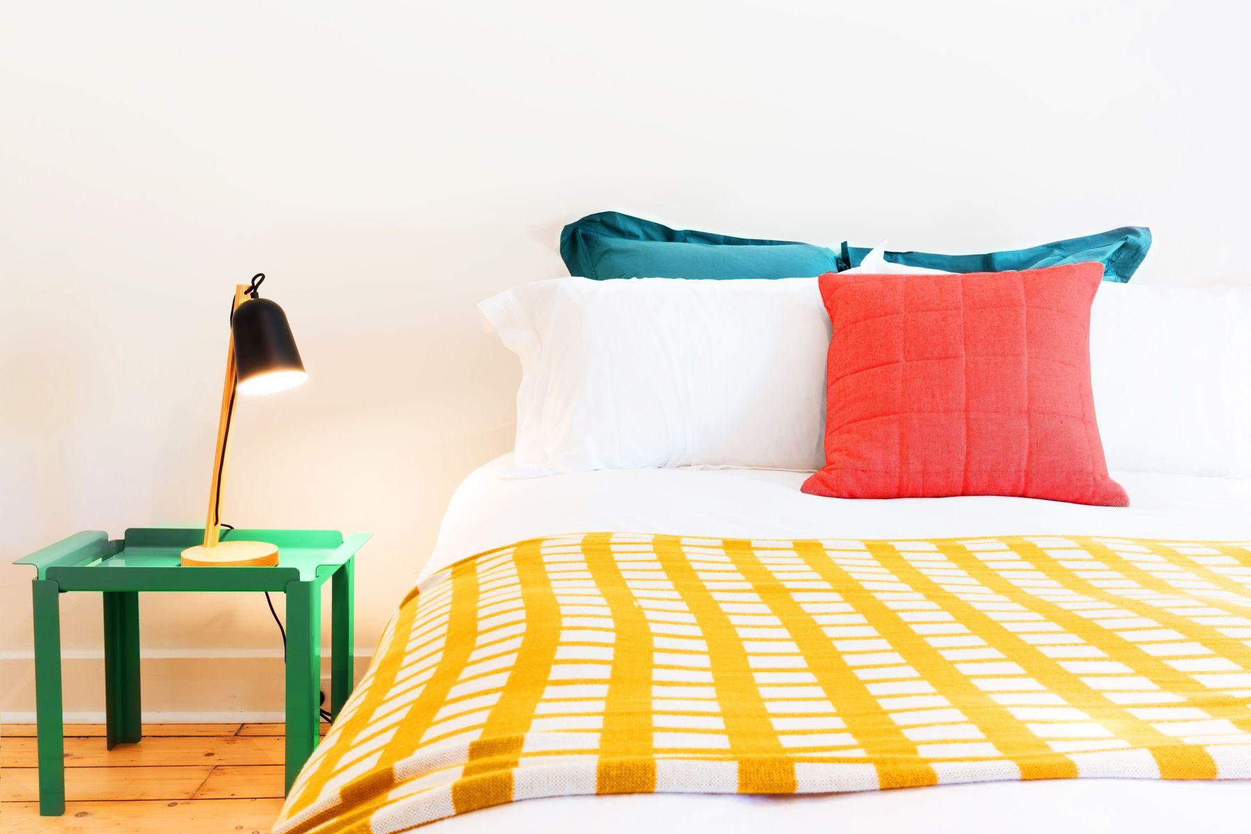 lit avec drap de lit rayé blanc et jaune et table de chevet verte avec abajour noir