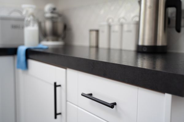 Close up of a kitchen counter and cabinet, cloth and spray cleaner in the background