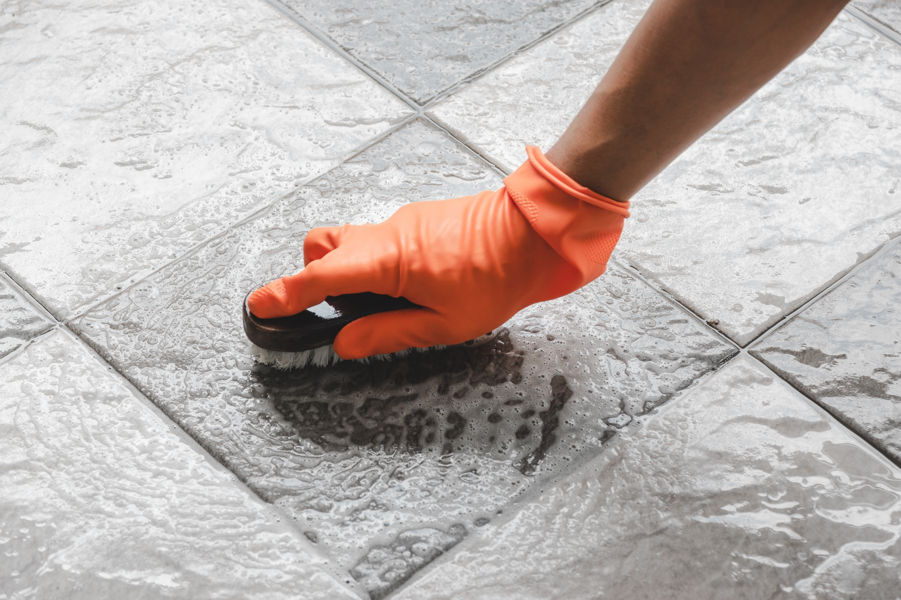 person wearing orange gloves scrubbing grout of bathroom tiles