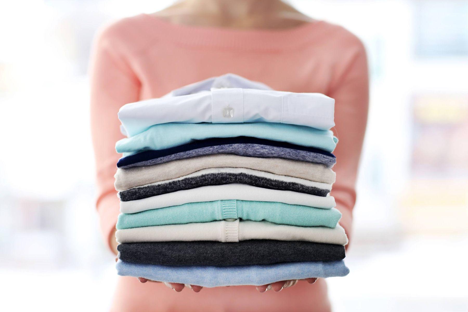 Mujer sujetando camisas lavadas, planchadas y apiladas