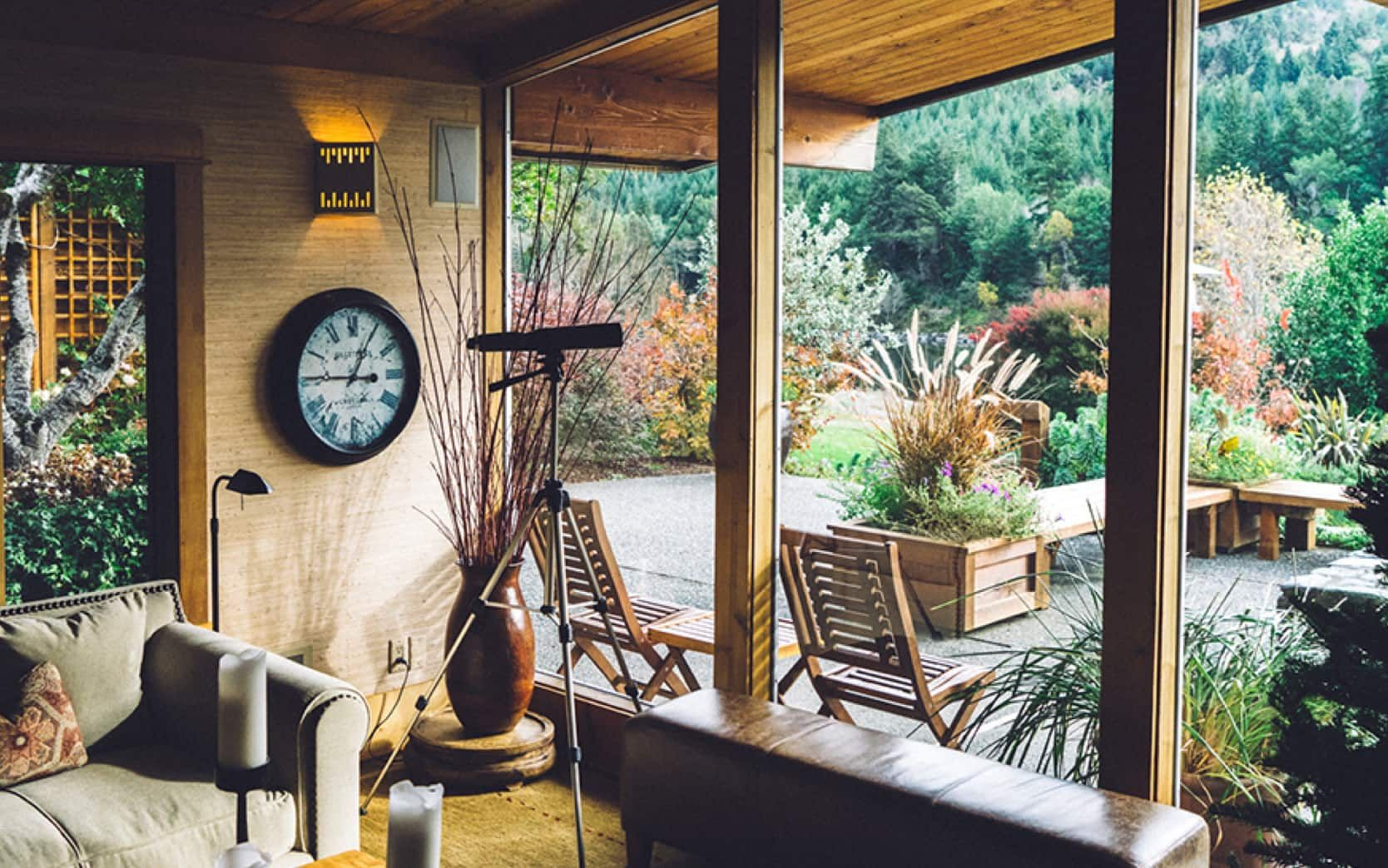 pokoj zařízený ve dřevě se skleněnými okny a výhledem do vnějšího prostoru