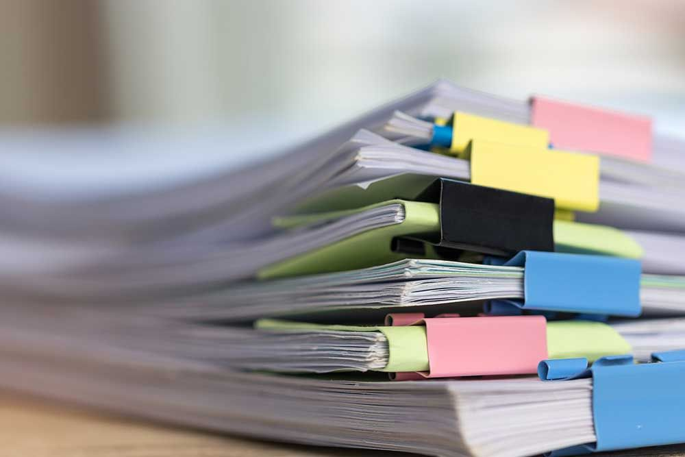 Piles of paper organised using colourful clips