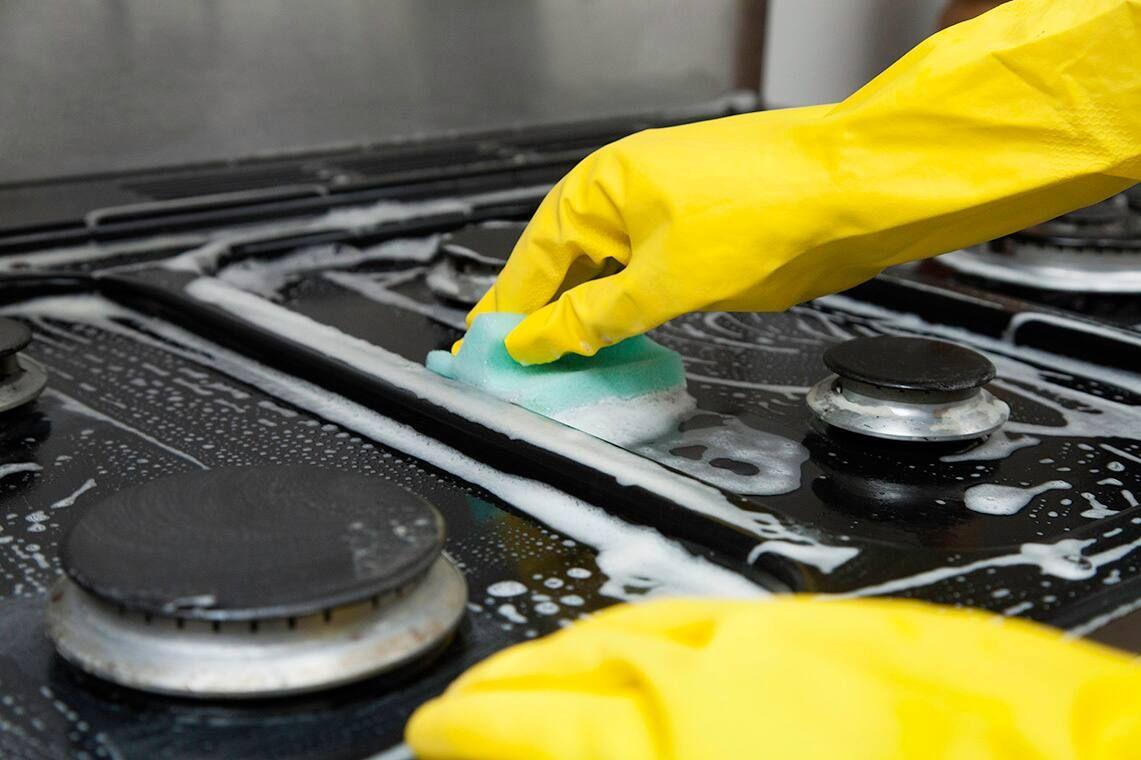 Pessoa esfregando fogão com esponja amarela