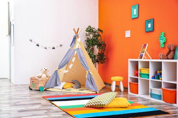 Sala com parede laranja com tenda infantil na esquerda e estante com brinquedos na direita e tapete colorido no centro