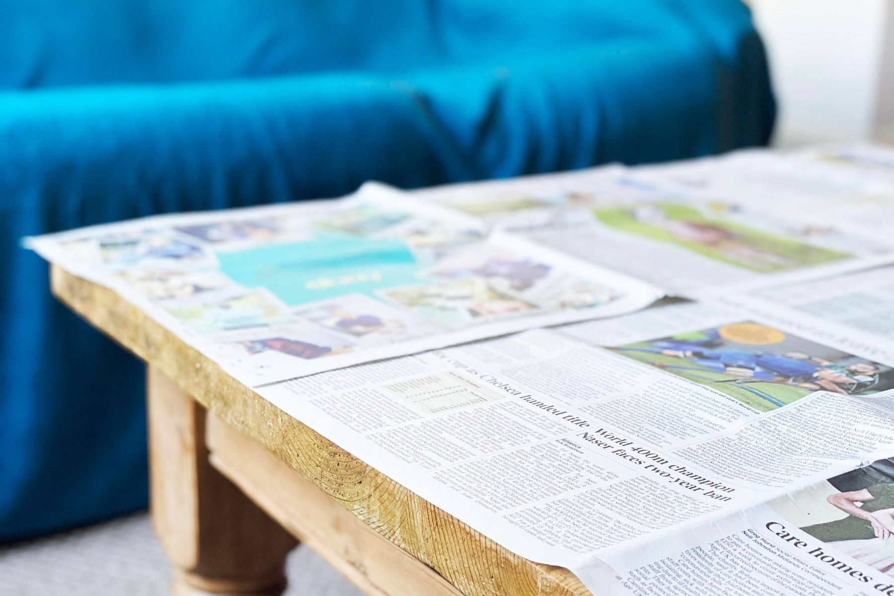 Coffee table covered in newspaper