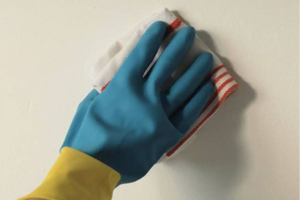 Person wearing gloves wiping a wall