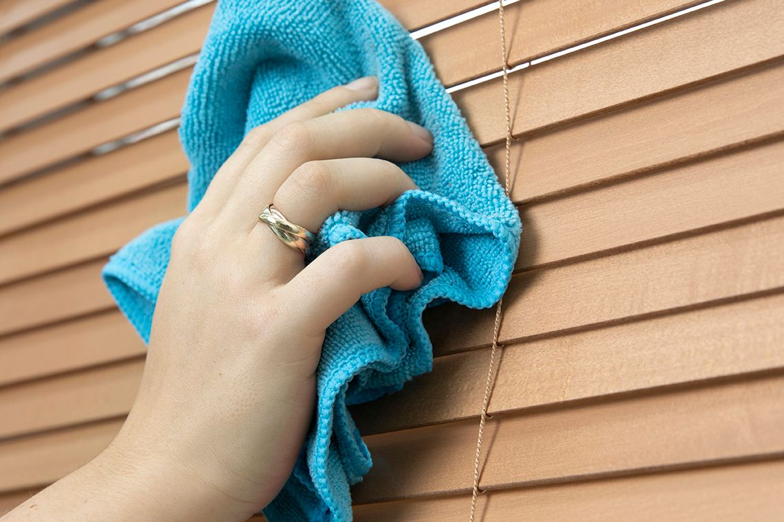 hand dusting blinds with a blue cloth