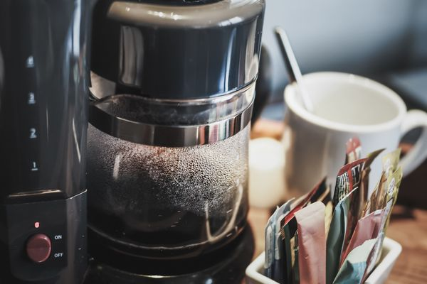 How to clean a coffee machine: coffee maker with magazines in the background