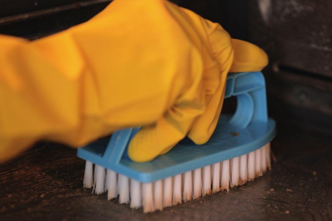 Pessoa com luva amarela esfregando chapa de ferro com uma escova de limpeza