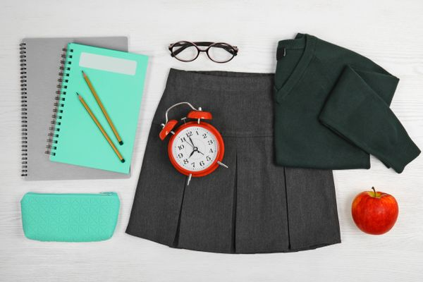 School uniform, stationery, apple, and alarm clock laid out on white wood