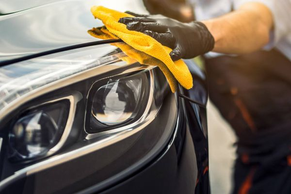 person cleaning car headlight with yellow cloth