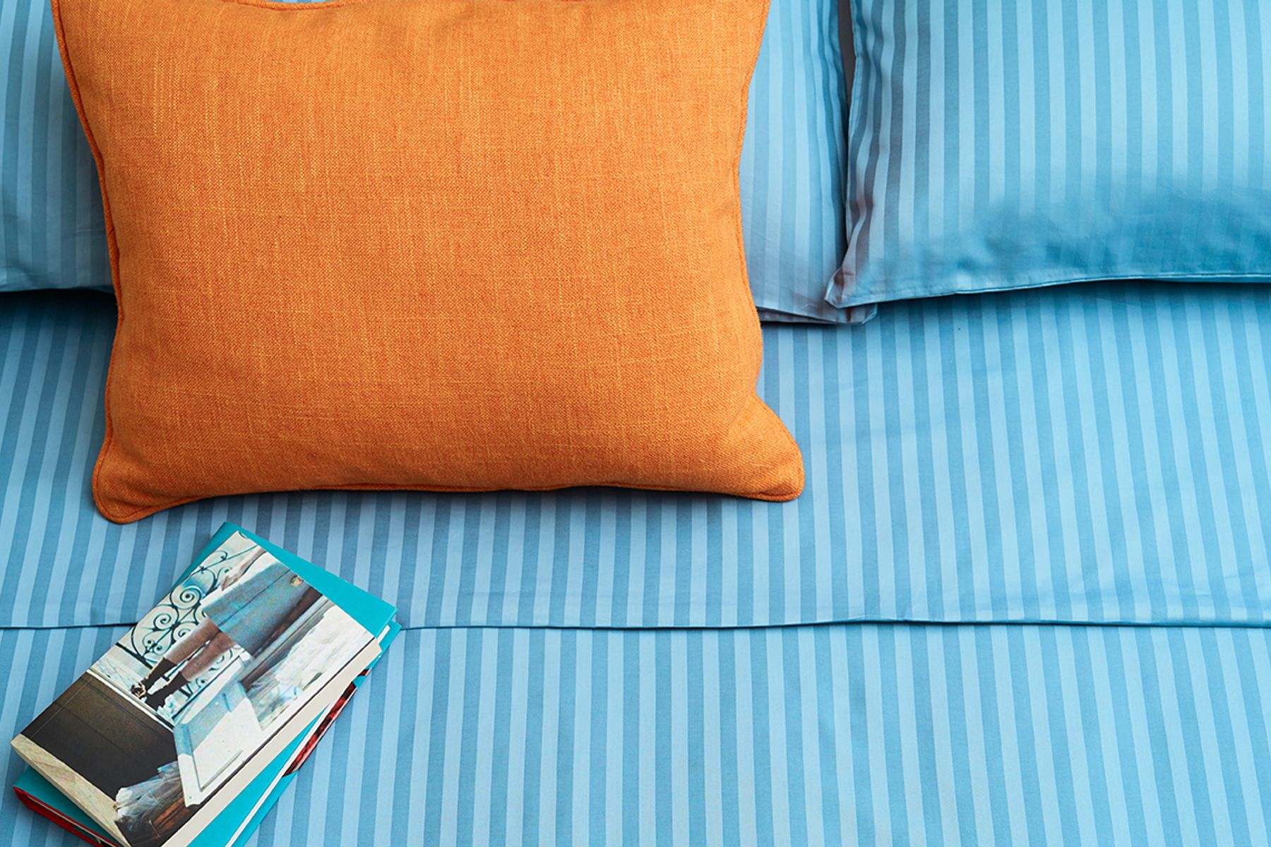 orange pillow on blue bedding and a book