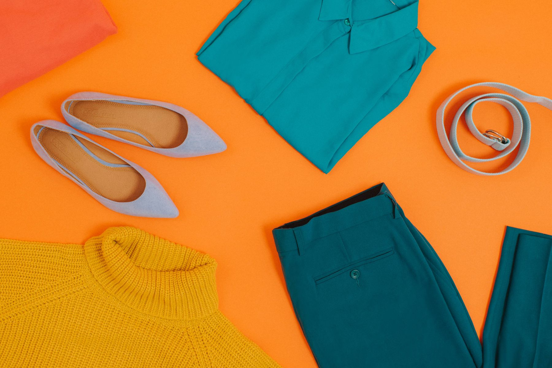Orange backdrop, with an assortment of women's folded clothes and accessories