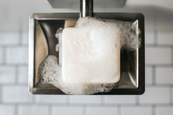Bar of soap in silver tray against white tile background