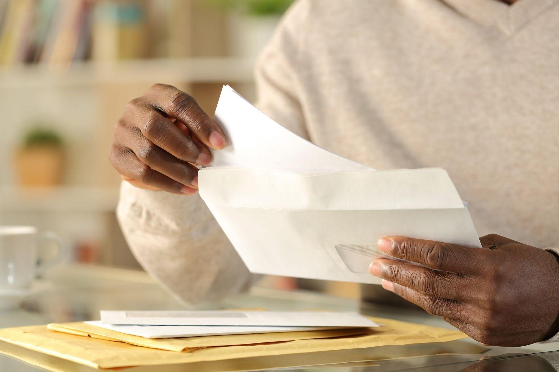 Homem segurando envelopes de correspondência