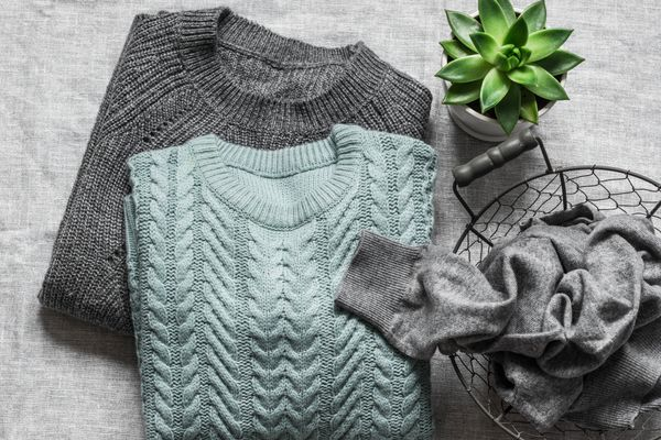 Grey and blue wool jumpers folded on a table with a plant and basket