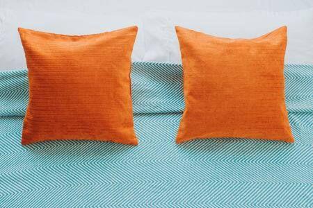 Almofadas laranjas sobre cama com lençol listrado branco e azul
