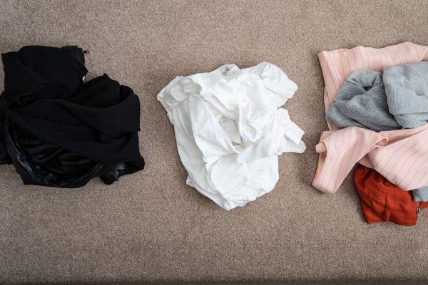 Pilha de roupas pretas, pilha de roupas brancas e pilha de roupas coloridas