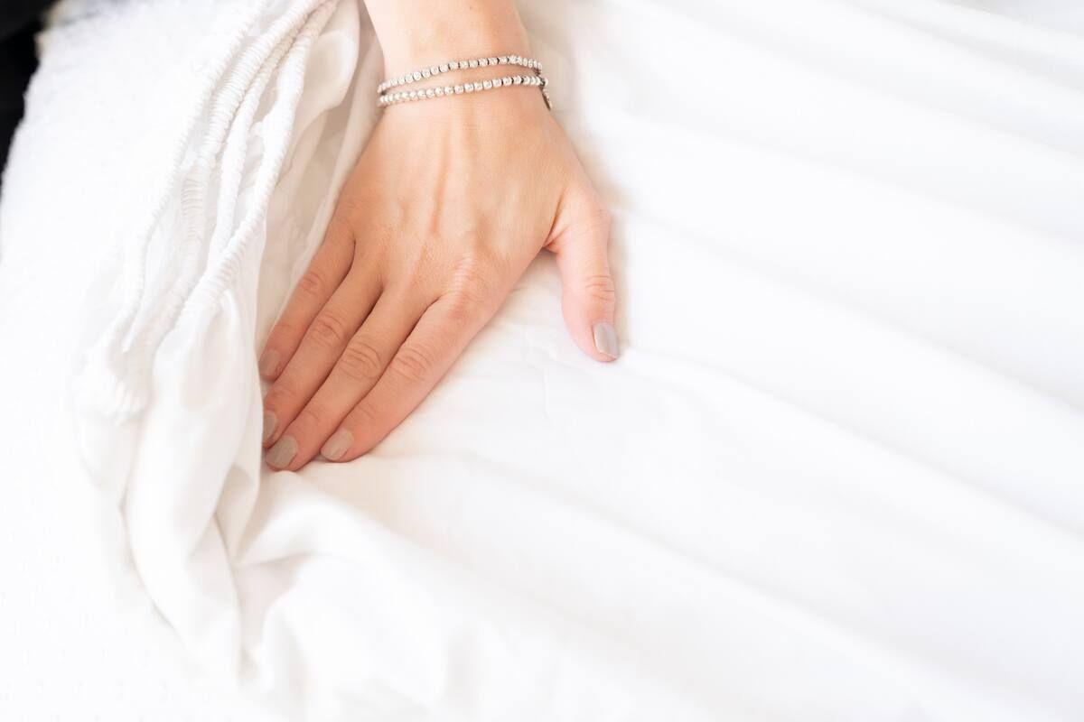 Mão alisa o lençol branco em colchão limpo