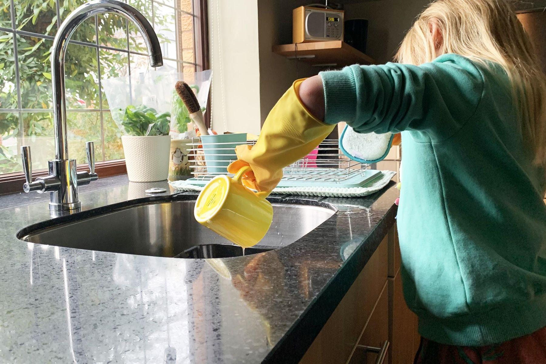 Criança lava caneca amarela na pia da cozinha