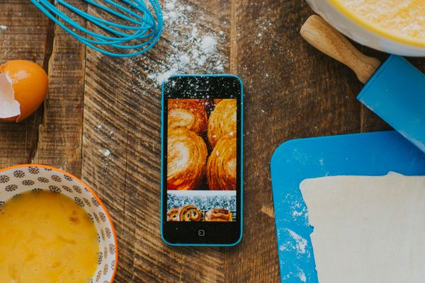 Smartphone on a table with baking ingredients around it