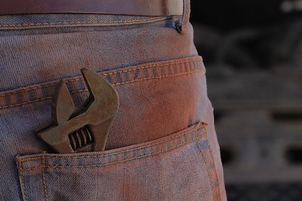 rusty trousers with a wrench in the pocket