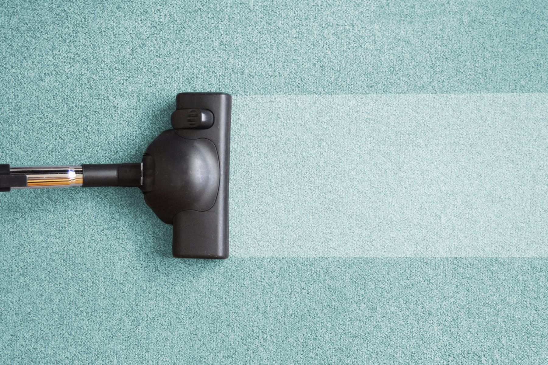 Vacuum cleaner on a carpet helping to remove burn marks