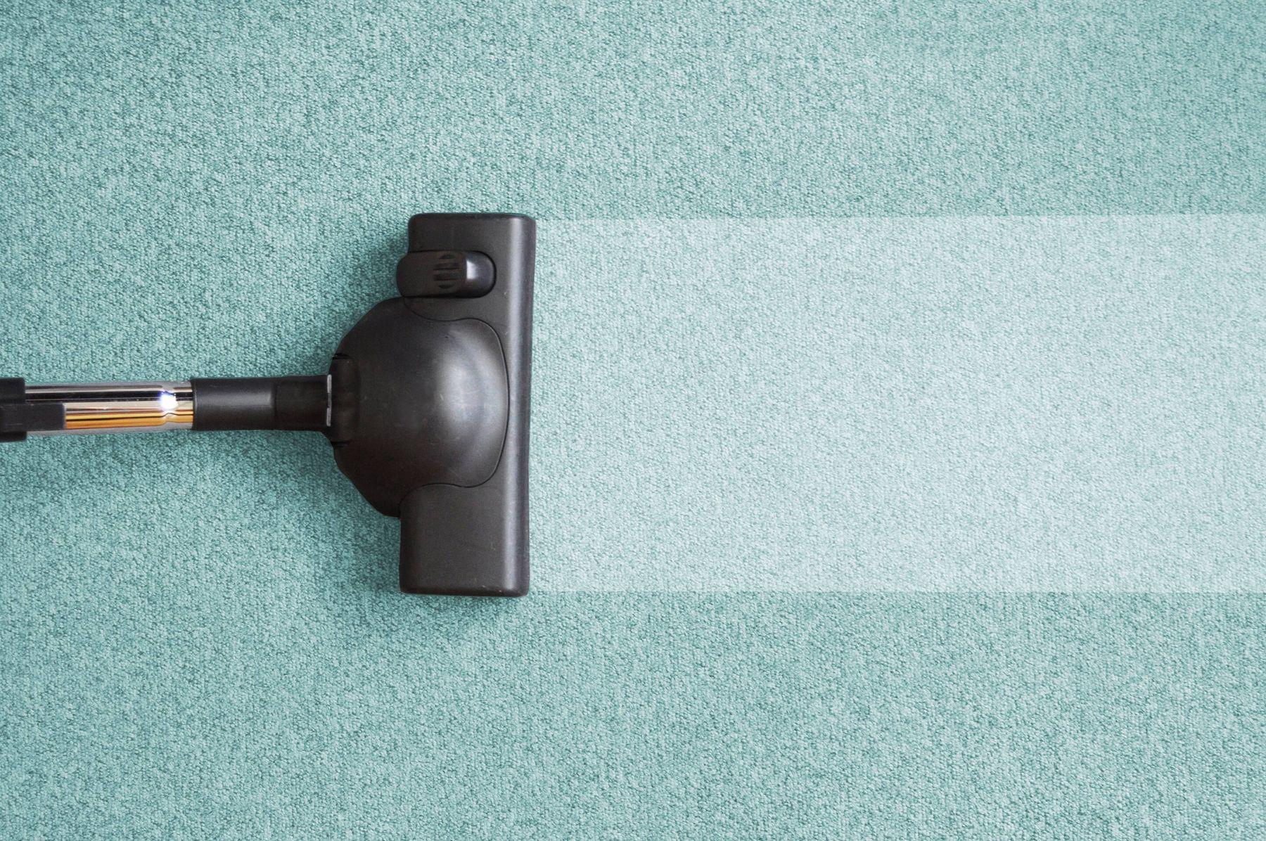 vacuum cleaner running over light blue carpet