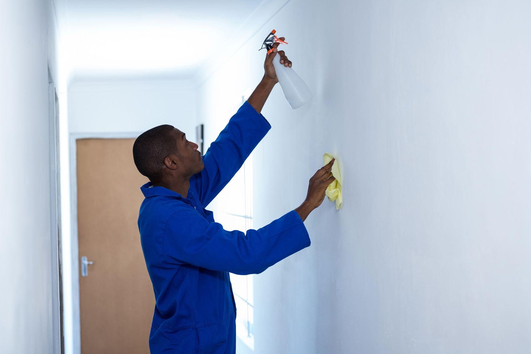 Homem de uniforme de limpeza borrifa produto na parede com uma mão e com a outra passa pano de limpeza