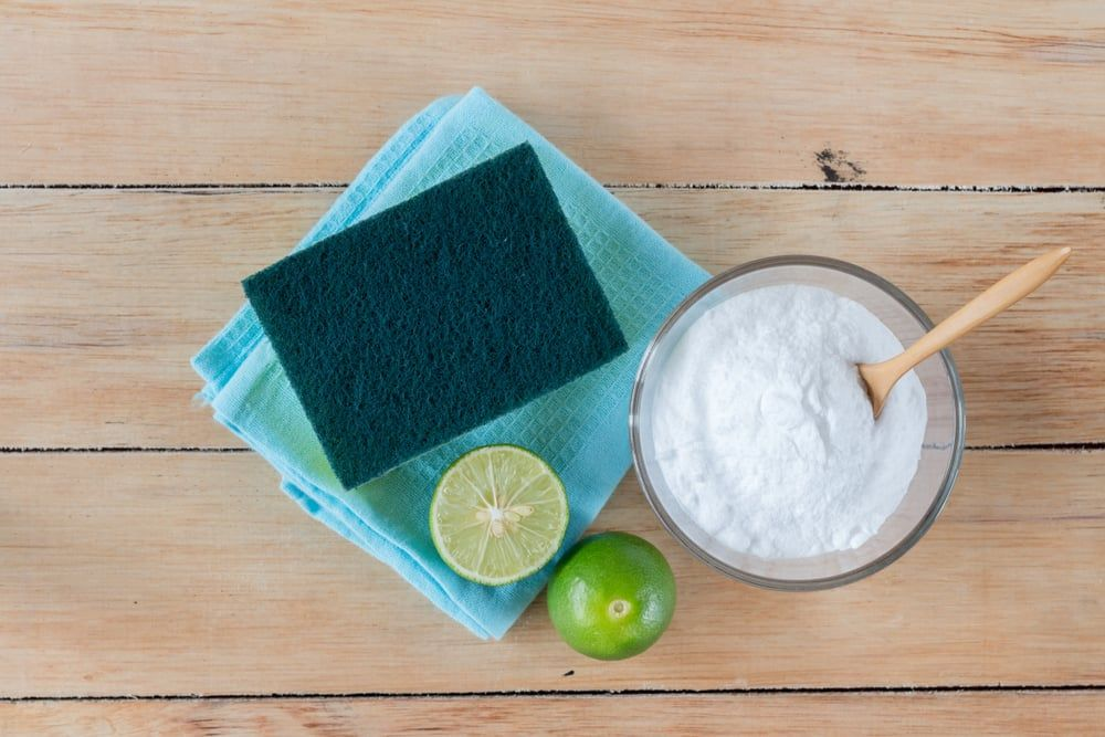 Limes and cleaning cloth on wooden surface