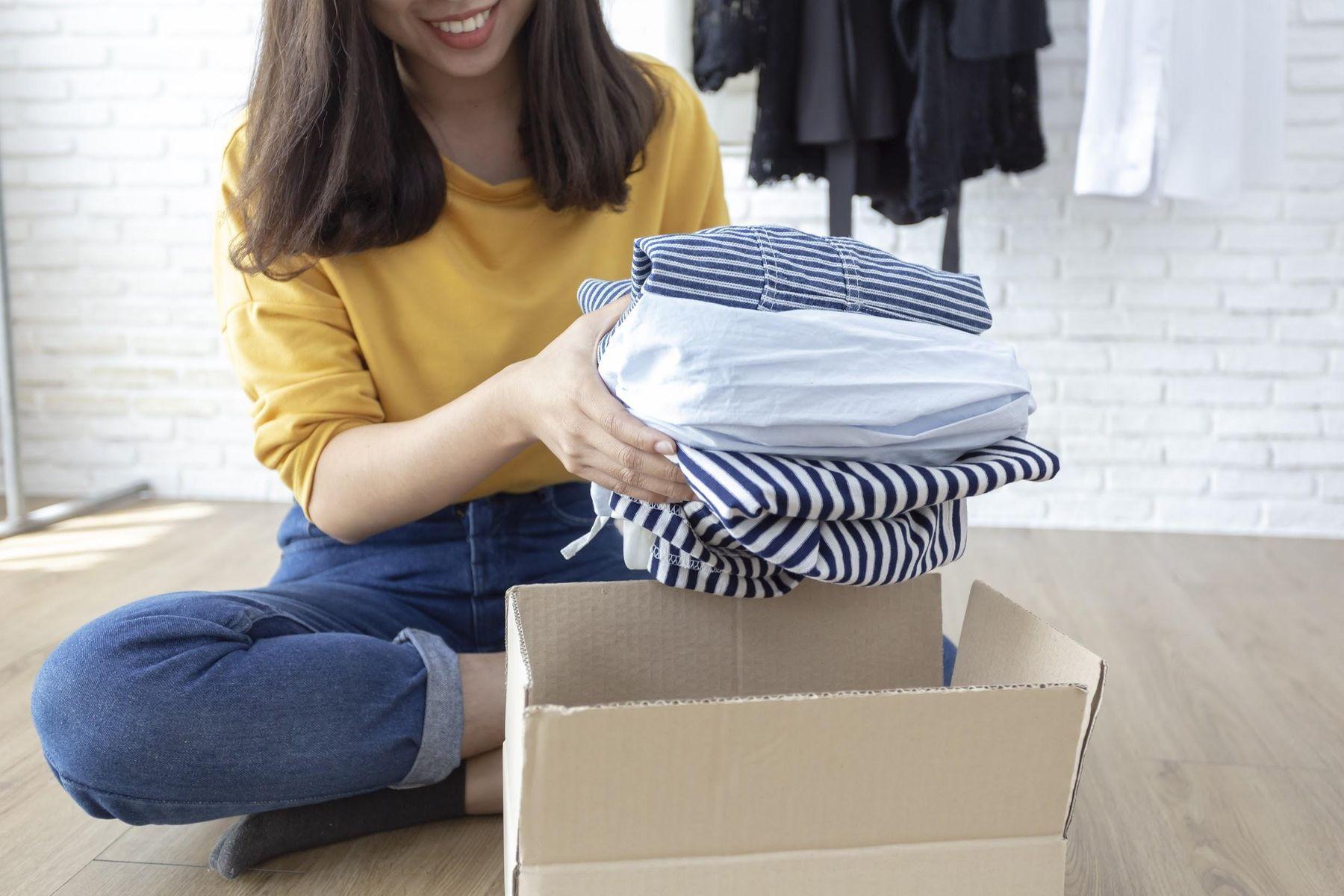 Mulher guardando roupas em caixa de papelão