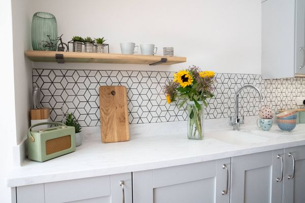 sunflower vase and wooden chopping board over white kitchen countertop