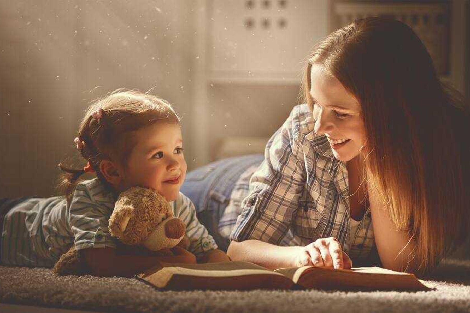 Mãe e filha sorrindo debruçadas sobre um livro