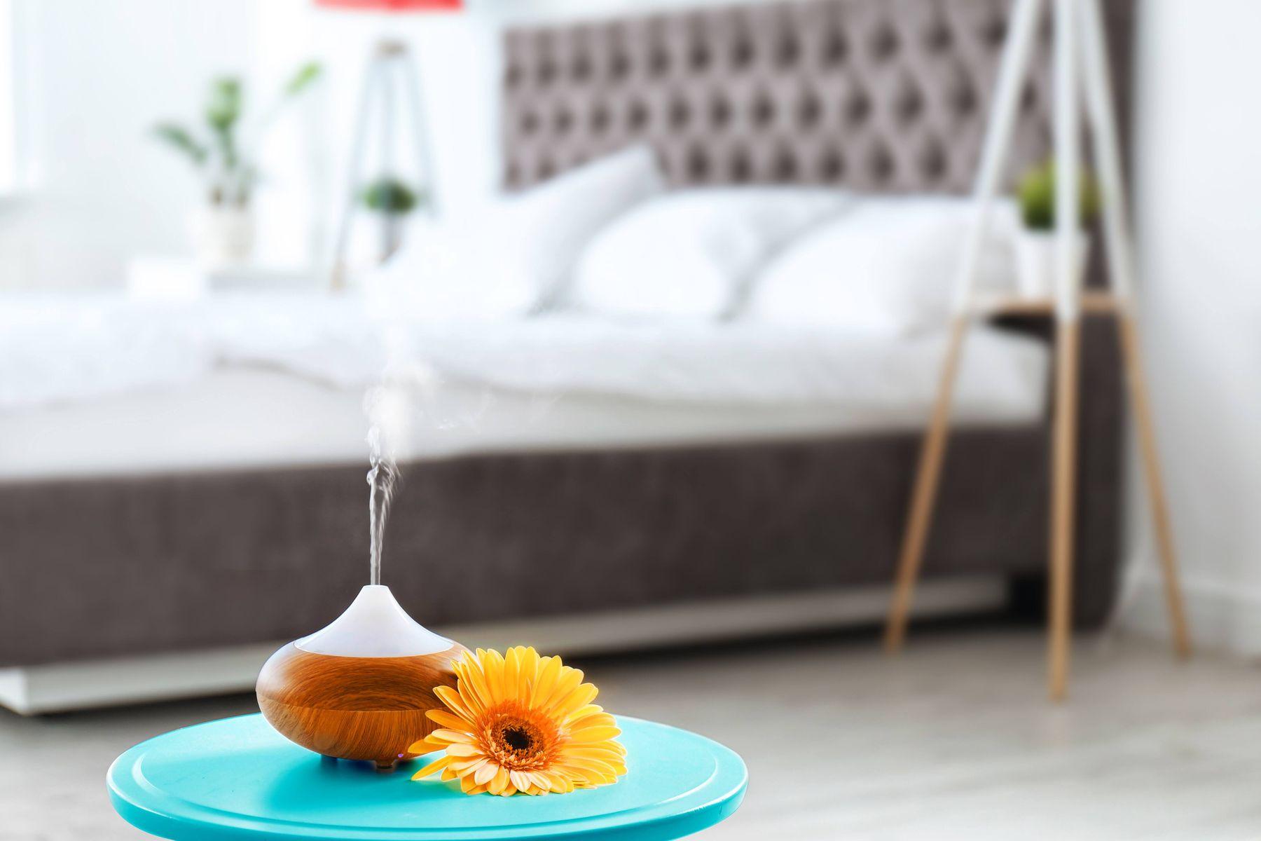 diffuseur d'huiles essentielles devant le lit gris et blanc