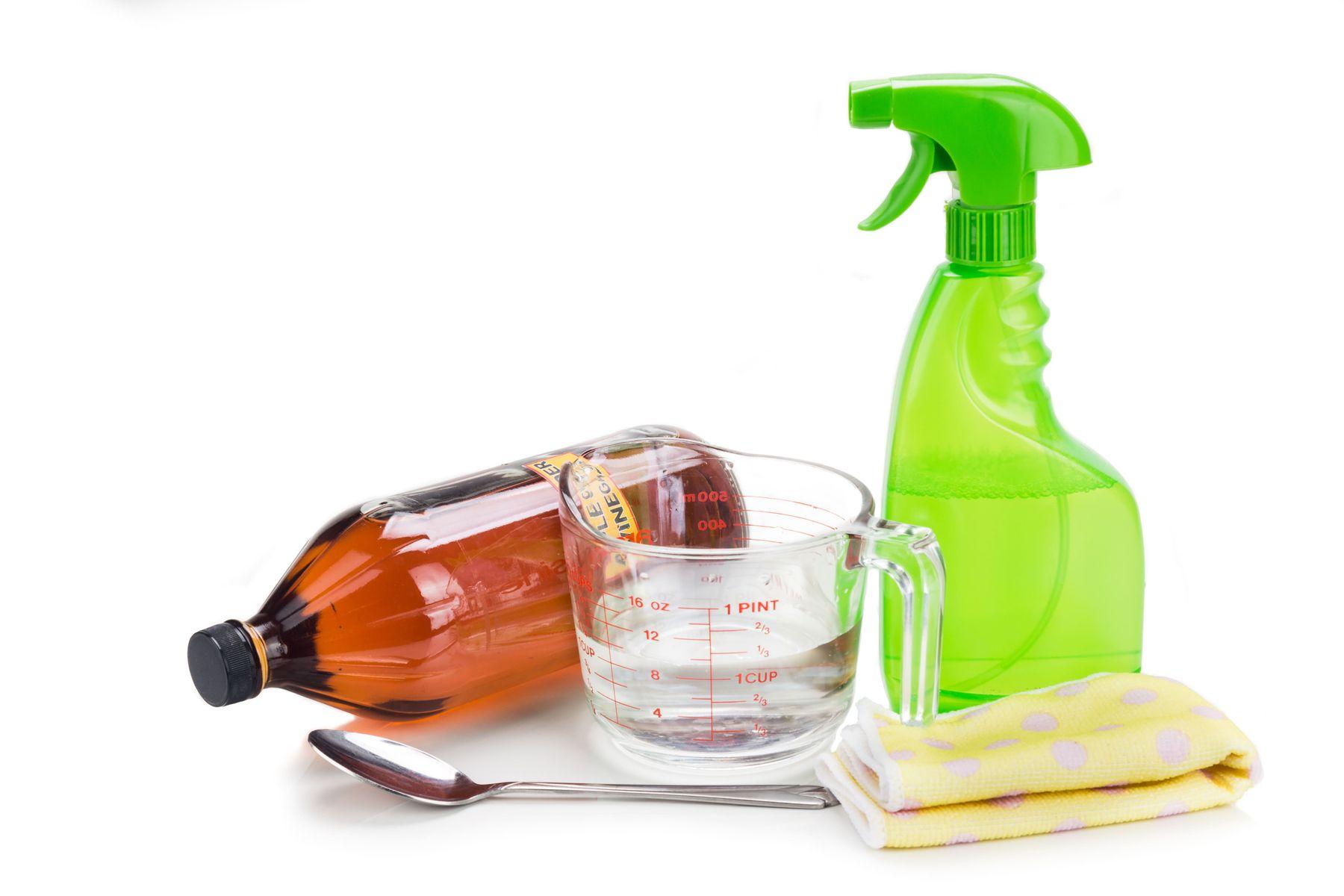 Frasco marrom e frasco com borrifador verde e um como pequeno com líquido transparente e uma colher e um pano amarelo sobre fundo branco