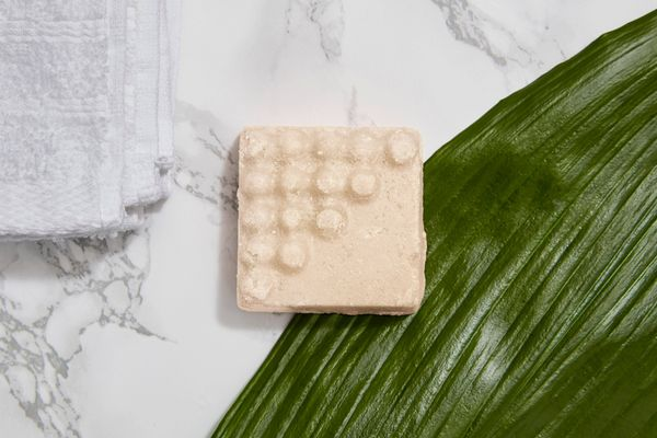 bar of gentle soap on green leaf and marble surface