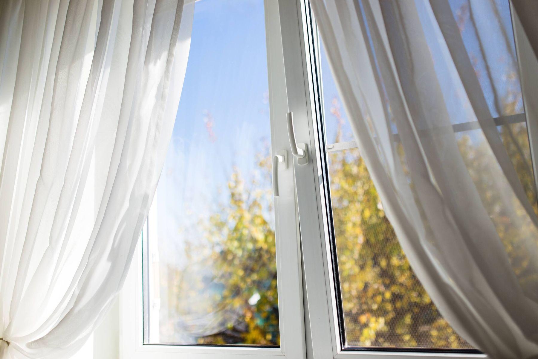 Fenster des Hauses mit hellen weißen Vorhängen