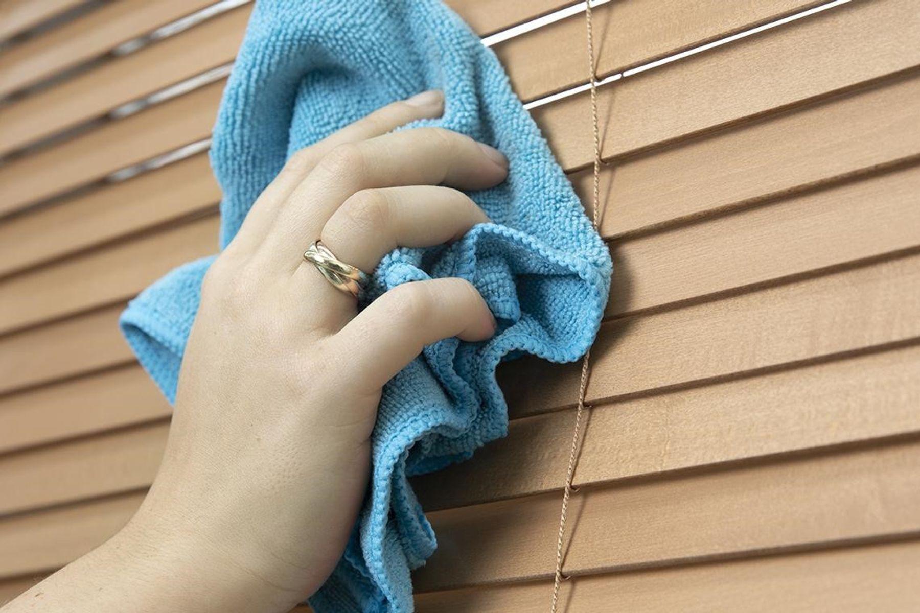 Mão passa um pano azul de limpeza na persiana de madeira
